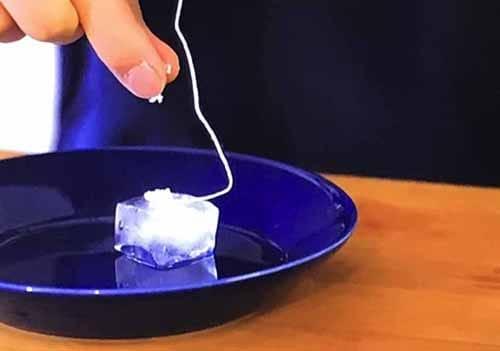 糸をつけた氷にしおをふりかける